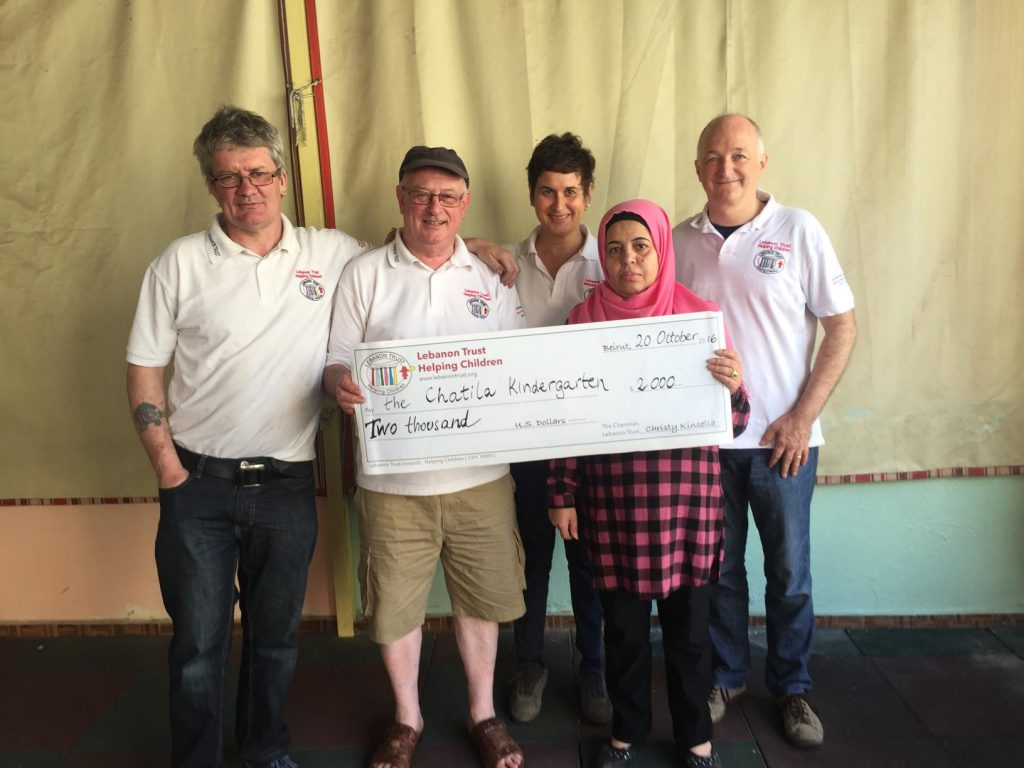 Volunteers of Lebanon Trust present Mariam, the head teacher, with a donation for the kindergarten.