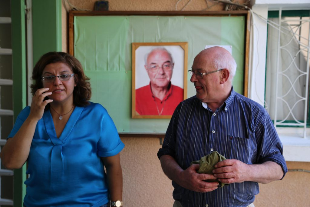FAID's founder Father Andeweg's portrait, flanked by Lina, FAID's Academic director, and Christy, Lebanon Trust's chairman